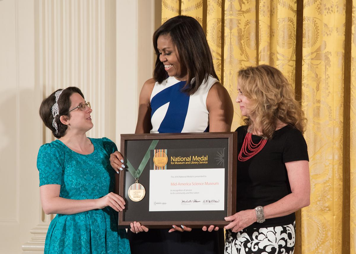 First Lady Michelle Obama presents the award to community member Casey Wylie and Mid-America Science Museum Executive Director Diane LaFollette.