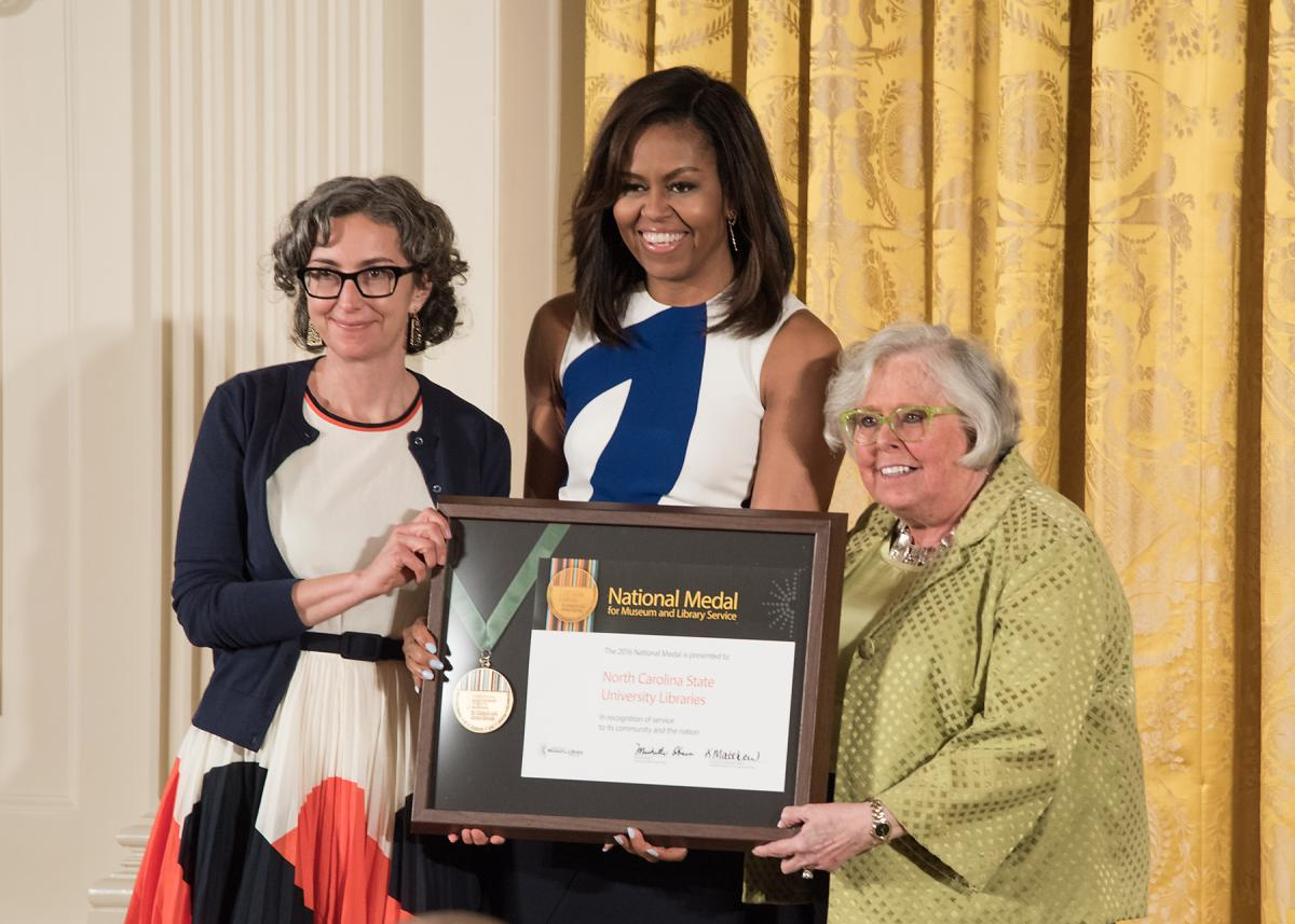 First Lady Michelle Obama presents the award to community member Marsha Gordon and Vice Provost and Executive Director of Libraries for the North Carolina State University Libraries Susan Nutter
