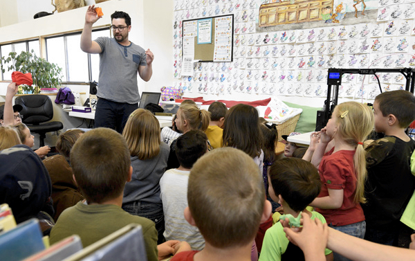 teacher demonstrates to class of elementary-age students