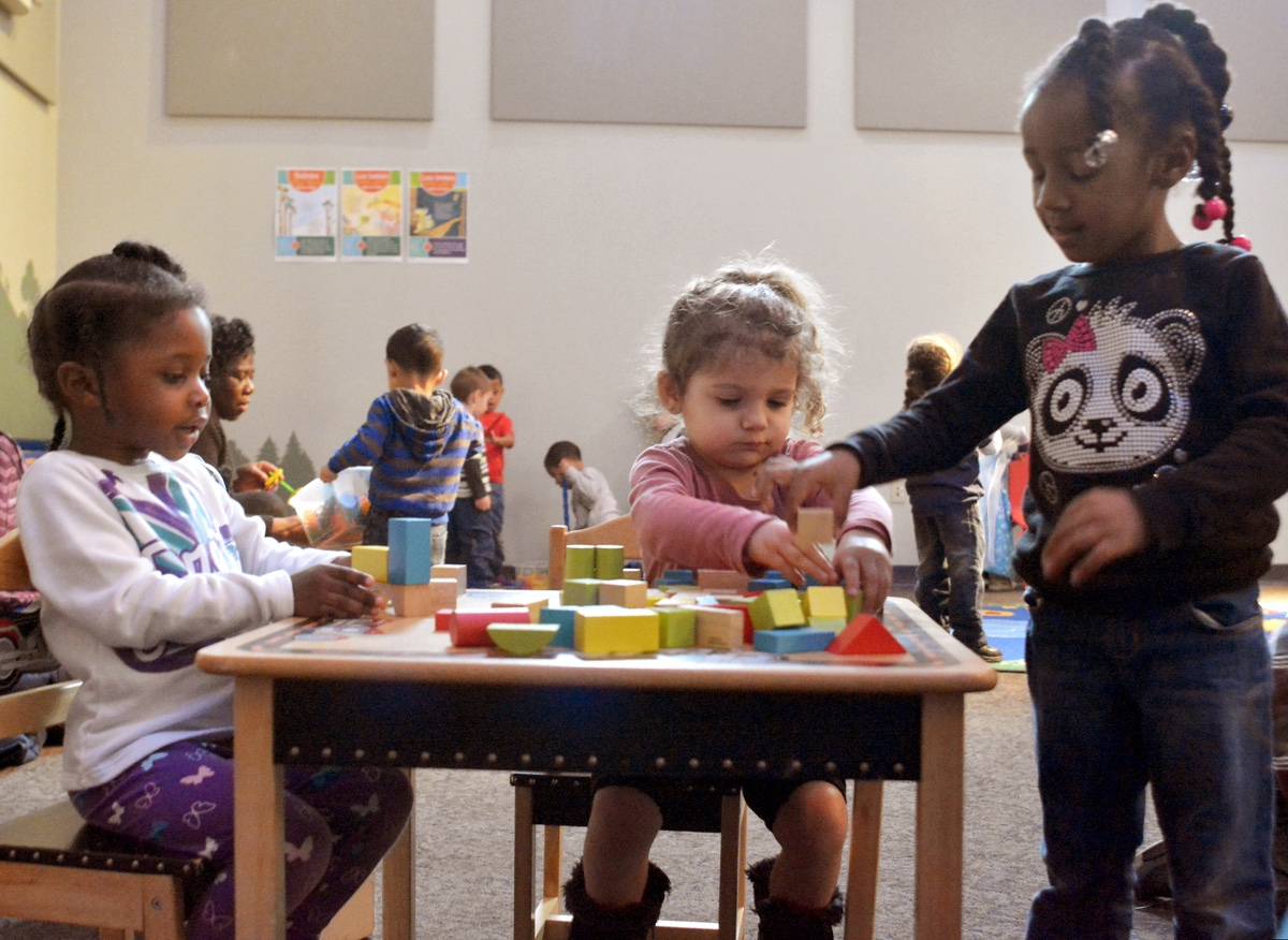 three pre-school age girls play with blocks in a community room
