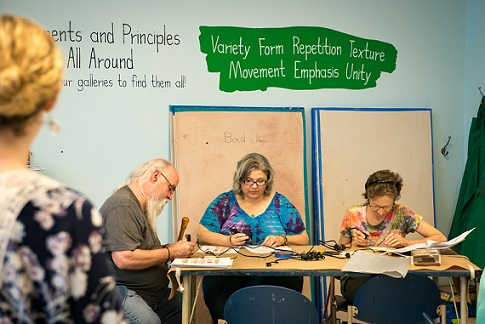 Older adults participate in a wood burning workshop