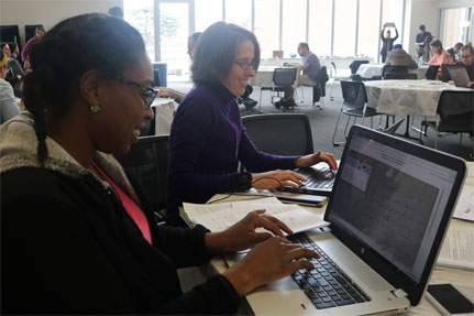 Woman and student in front of computer monitor