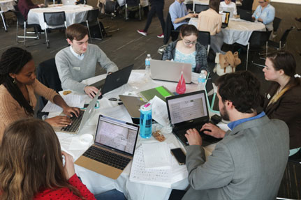 Group of students with computers sitting at table.