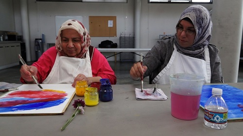 A mother and daughter work together on paintings during one of their art-making sessions.