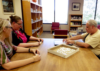 A visually-impaired patron plays Scrabble with library staff