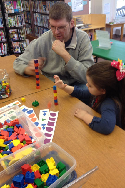 A young learner and her guardian learn about patterns and build towers at a Kingdom of Why science station.
