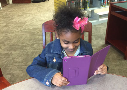 Six-year-old Zyasia Salter explores the Open eBook app at the Seymour Wilson Branch Library, New Haven Free Public Library. The system is purchasing 3 tablets for each of its five locations to accommodate in-library use and to offer content to kids who don't have devices at home. Photo courtesy of Courtland Seymour Wilson Branch Library, New Haven Free Public Library (CT).