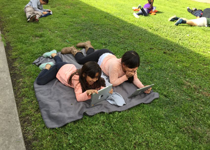 "Veronica Hidalgo of Magee Academy asked her students to end the week with 30 minutes of unwinding with a good read. She told them, ""Grab an iPad, find a spot outside, launch Open eBooks, and enjoy the books you selected."" Photo courtesy of Magee Academy."