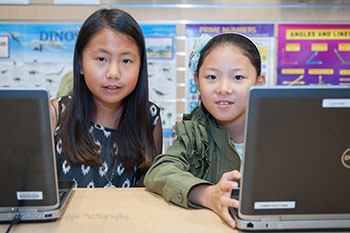 Two girls sitting at a desk with laptops. Photo courtesy of the San Mateo Public Libraries.