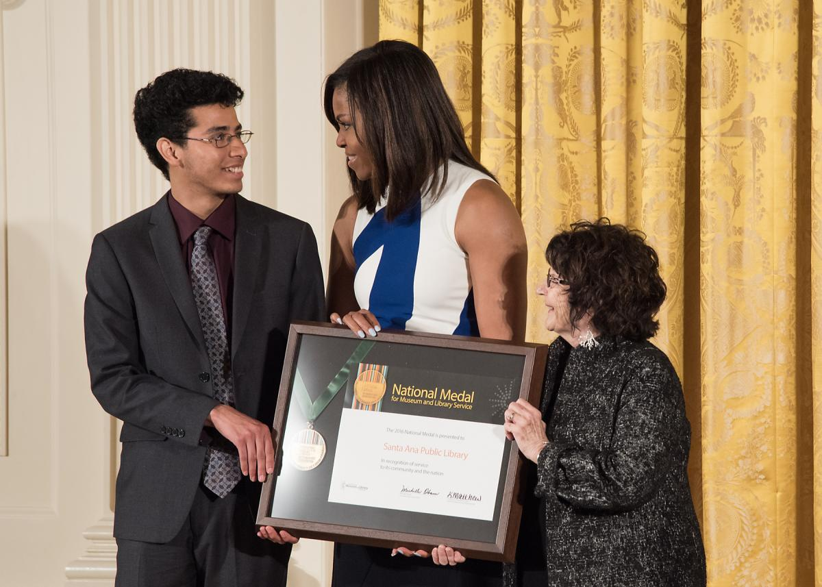 Community member Victor Gudiel and Santa Ana Public Library Director Heather Folmar accept the award from First Lady Michelle Obama during the ceremony.