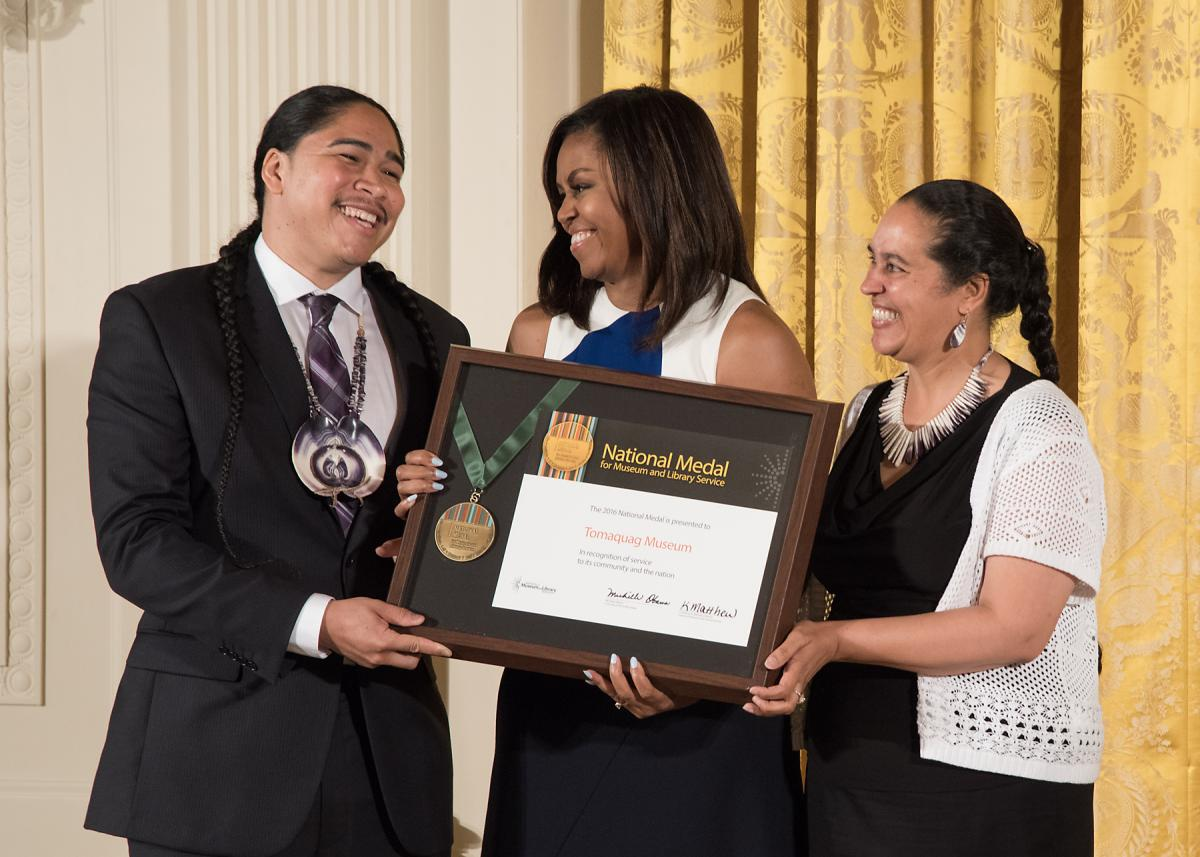Community member Christian Hopkins celebrates with Tomaquag Museum Executive Director Loren Spears after accepting the award from First Lady Michelle Obama.