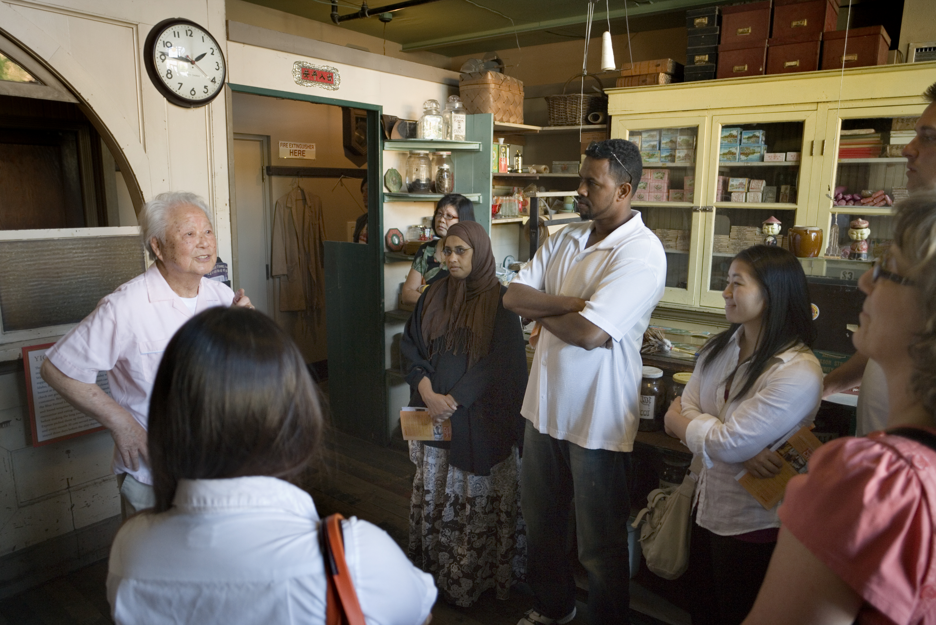 A senior man talks to a tour group at the Wing Luke Museum.