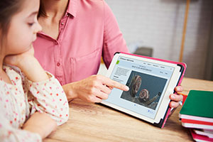 Woman and child sitting at desk with smart device